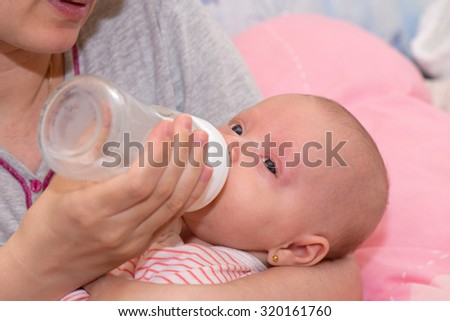 Mother feeding her baby with a milk bottle