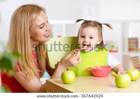 Mother feeding her child healthy food - stock photo
