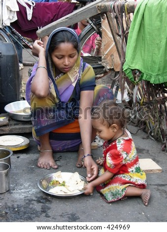 mother feeding her child on the street - stock photo