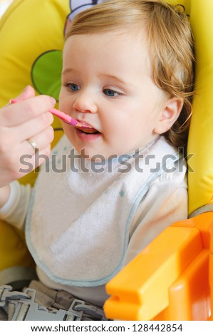 Mother feeding her cute baby at home - stock photo