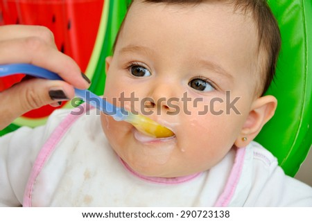 Mother feeding her cute hungry baby girl  - stock photo