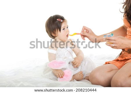 Mother feeding hungry baby dressed in white, isolated on white background - stock photo