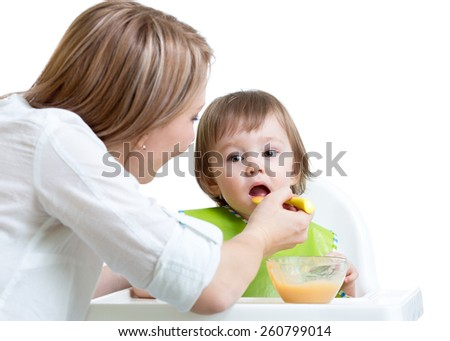 mother feeding kid boy with spoon isolated on white - stock photo