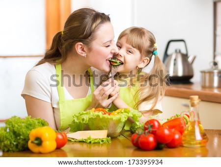 mother feeding kid vegetables in kitchen - stock photo