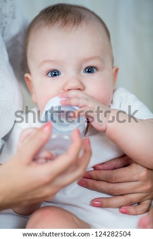 mother feeding milk his baby infant from bottle