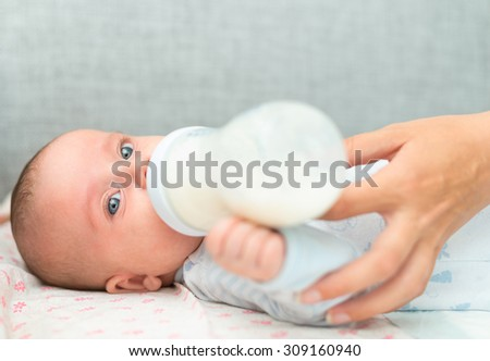 Mother feeding newborn baby from the bottle.