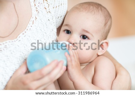 mother feeds baby boy milk from bottle - stock photo