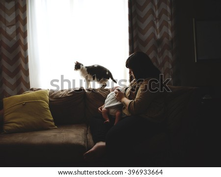 Mother feeds baby by a window and cat comes too - stock photo