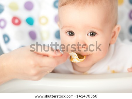 Mother feeds funny baby from a spoon - stock photo