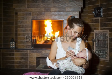 mother feeds her baby at the fireplace. - stock photo