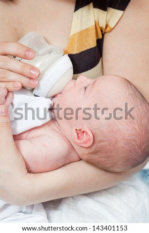 Mother feeds the chest baby from a children's small bottle
