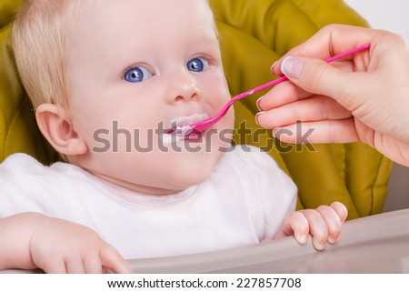 Mother feeds the child with a spoon