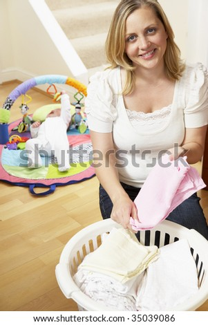 Mother Folding Baby Clothes At Home - stock photo