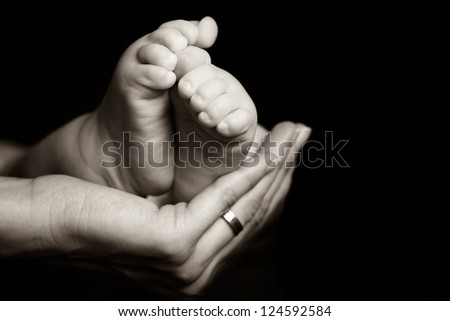 Mother gently holding her baby foot - black and white photograph - stock photo