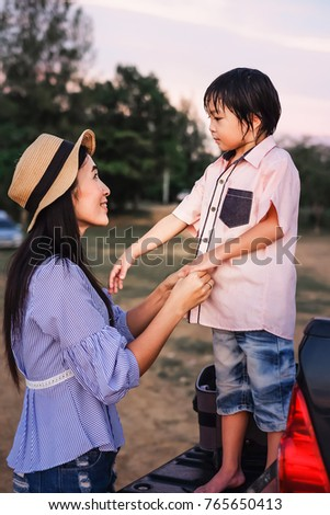 mother getting dress for her son.Asia woman take care a cute boy during relaxing on holiday.