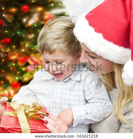Mother give little son christmas gift. - stock photo