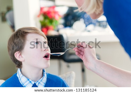 Mother give medicine to son with spoon - stock photo