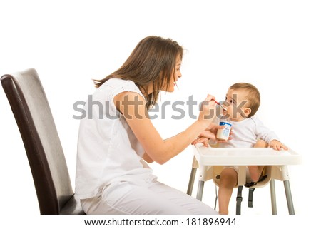 Mother gives her baby to eat yogurt isolated on white background - stock photo