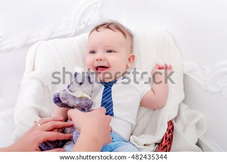 Mother gives the baby a teddy bear . smiling baby to mom