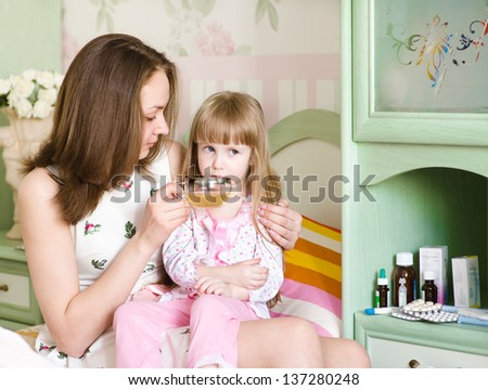 mother gives to drink to the sick child - stock photo