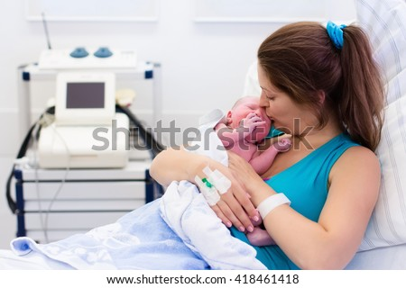 Mother giving birth to a baby. Newborn baby in delivery room. Mom holding her new born child after labor. Female pregnant patient in a modern hospital. Parent and infant first moments of bonding. - stock photo