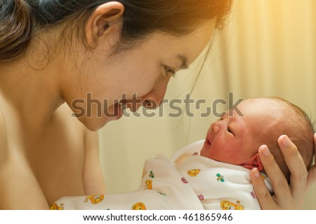 Mother giving birth to a baby newborn baby in delivery room mom holding her