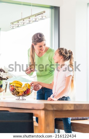 Mother giving child fresh fruits for healthy living in home kitchen - stock photo