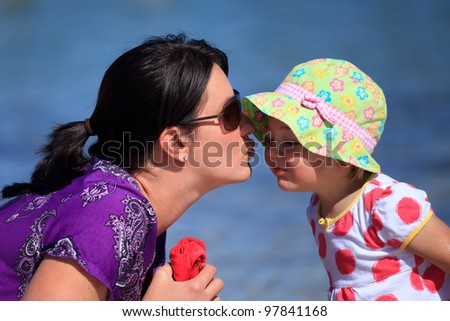 Mother giving daughter a kiss at the beach - stock photo
