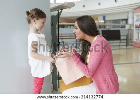 Mother giving daughter paper shopping bag - stock photo