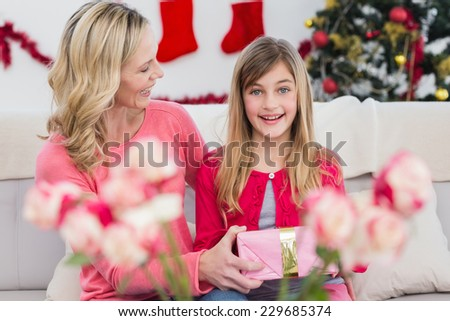 Mother giving her daughter a christmas gift at home in the living room - stock photo