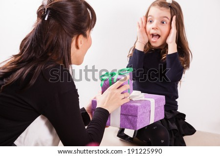Mother giving her daughter a surprise gift. - stock photo