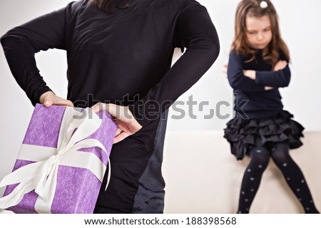 Mother giving her daughter a surprise gift. Daughter is angry in the background. - stock photo
