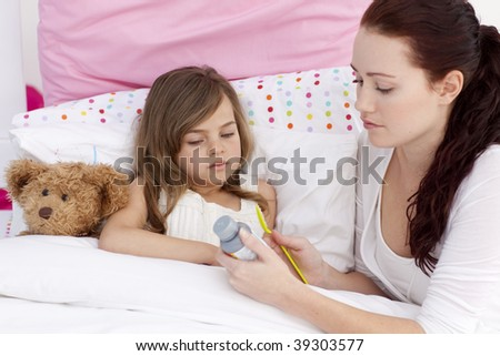 Mother giving her daughter cough medicine in bed