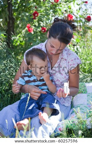 Mother giving homeopathic medicine to her son. Shallow DOF, focus is on their faces.