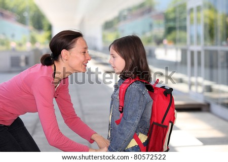 Mother giving kiss goodbye to children - stock photo