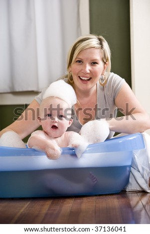 Mother giving 7 month old baby a bath - stock photo