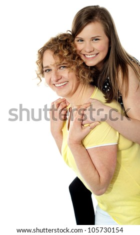 Mother giving piggy ride to her cute beautiful daughter. All on white background