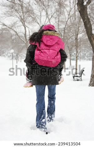 Mother Giving Piggyback Ride to Daughter in Snow - stock photo