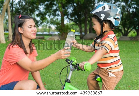 Mother giving the drinking water to boy on the bicycle in garden