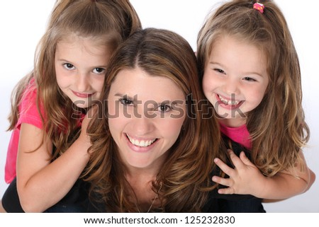 Mother giving two daughters a piggy back ride, wearing pink and black in studio on white isolated background - stock photo