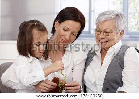 Mother, grandmother and little girl sewing, doing needlework. - stock photo