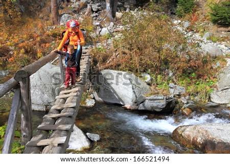 Mother guiding a small boy across wooden bridge - stock photo