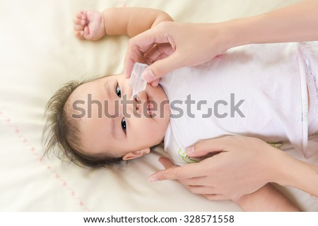 Mother hand combing hair for her Baby