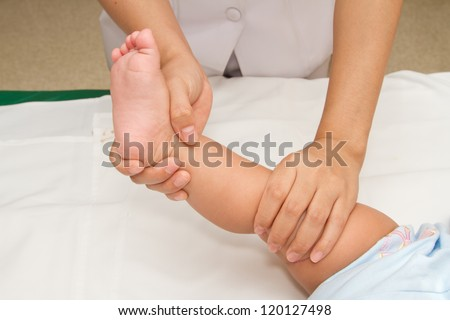 Mother hand massaging foot of her baby on white background - stock photo