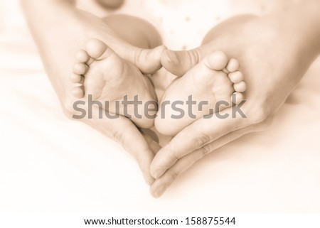 Mother hands and baby feet - stock photo