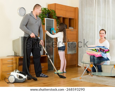 Mother, happy father and little girl doing general cleaning indoors - stock photo