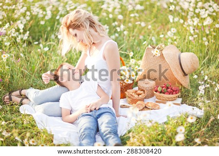 Mother having picnic with his son in the blossom field of camomile in Crimea region - stock photo