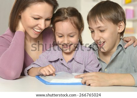 Mother  help children do their homework at table - stock photo