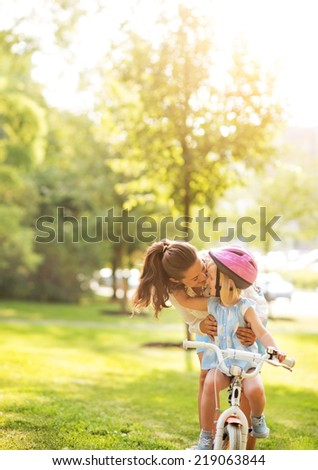 Mother helping baby girl riding bicycle outdoors - stock photo
