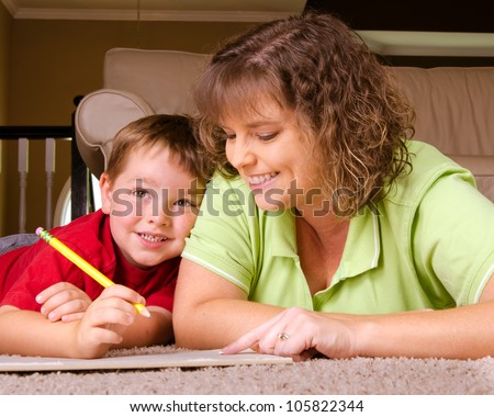 Mother helping child with writing lesson for school while at home - stock photo